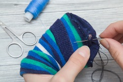 Hand with a needle and thread darning a sock. Handmade.