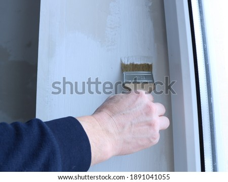 hand with a paint brush applies a layer of white paint to the surface of the side window slope close-up, redecoration of the room, manual renewal of staining, work with water-based white paint Сток-фото ©