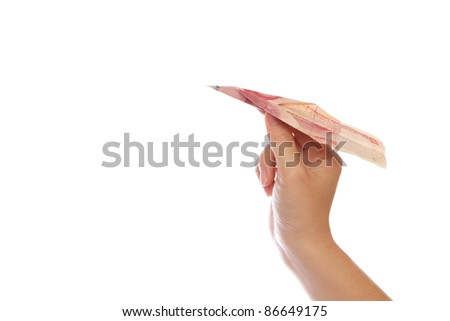 hand with a paper airplane made by Chinese Money yuan