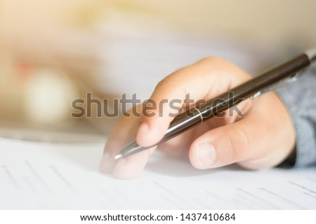 Hand with a pen in office.