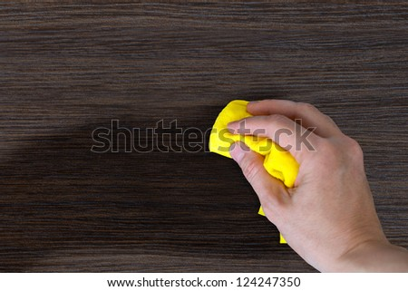 hand with a rag to dust the wood furniture