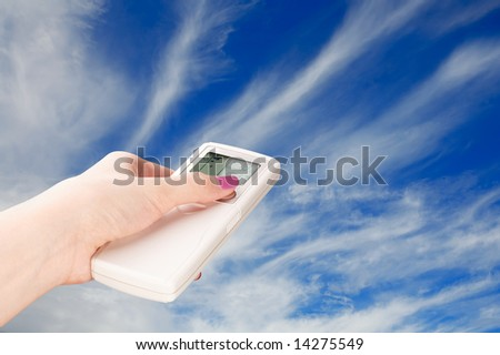 Hand with a remote control directed on the cloudy sky