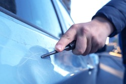 Hand with a screwdriver or a large nail scratching the paint surface on the vehicle door, close-up. The criminal is engaged in vandalism. Revenge neighbor, business partner or offended lover