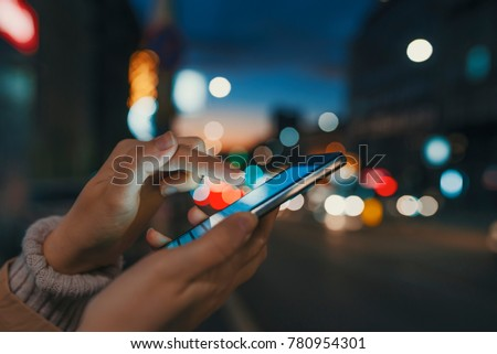 Hand with a smart phone in a dark. Female using her mobile phone, city skyline night light background. Girl pointing finger on screen smart phone on background illumination color light in night city