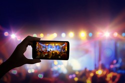 Hand with a smartphone records live music festival and taking photo of concert stage live concert luxury party in facebook live.