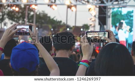 Hand with a smartphone records live music festival, Taking photo of concert stage, live concert, music festival