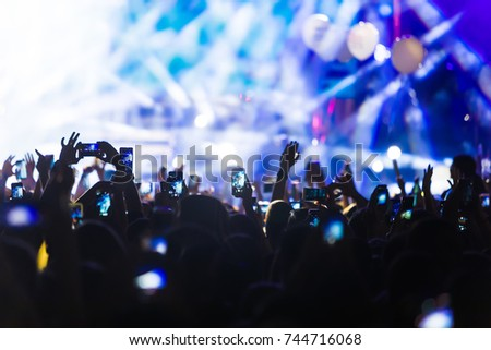 Hand with a smartphone records live music festival, Taking photo of concert stage, live concert, music festival, happy youth, luxury party, landscape exterior #744716068