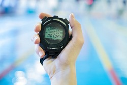 hand  with a stopwatch during competitions in the swimming pool