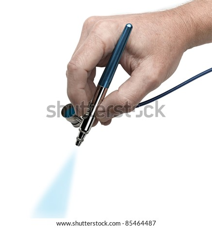 Hand with airbrush painting with cyan color - stock photo