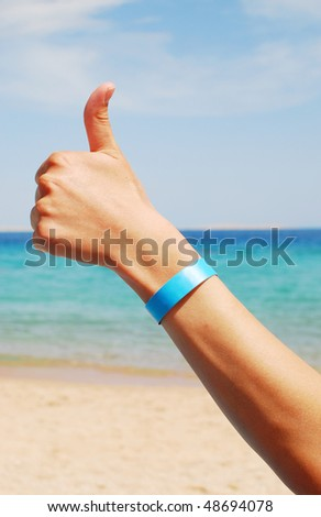 hand with all inclusive bracelet over sea background