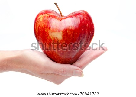 Hand with an apple in the form of heart