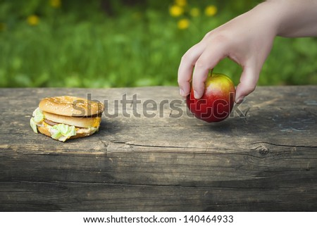 Hand with apple near the burger