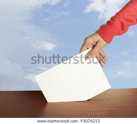 Hand with ballot and box isolated on sky