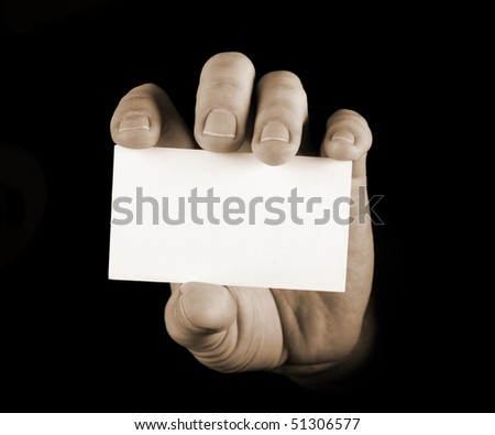Hand with black business card on black background