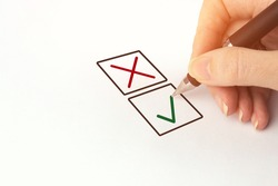 Hand with black pen choosing one of two options answer. Person Marking in a Checkbox
