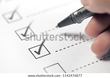Hand with black pen marking on checklist box.