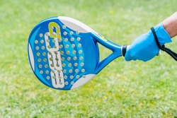 Hand with blue latex protection gloves holding a paddle racket with the green field background. Returning to sports after coronavirus confinement.