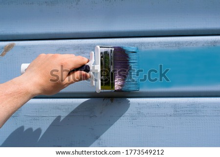 Hand with blue paint brush on the wooden wall