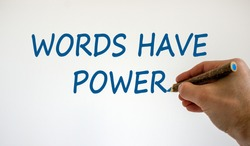 Hand with blue pencil writing 'words have power', isolated on beautiful white background. Concept. Copy space.