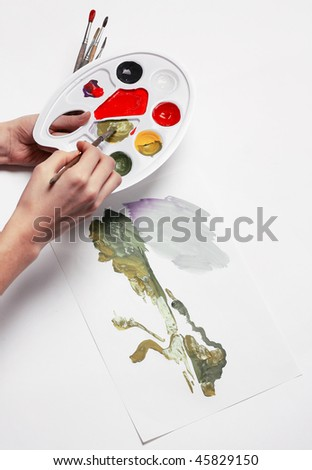 Hand with brush and palette - stock photo