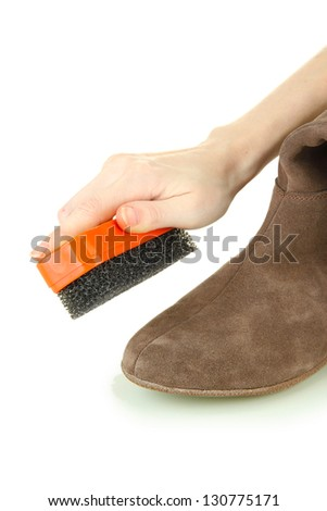 Hand with brush cleaning suede shoes, isolated on white