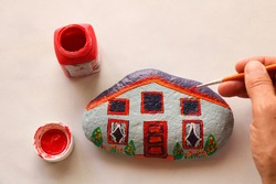 hand with brush painting stone as stylized home, white background and copy space