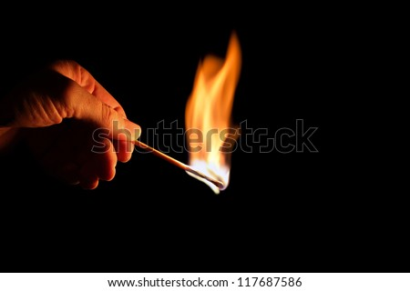 hand with burning match on black
