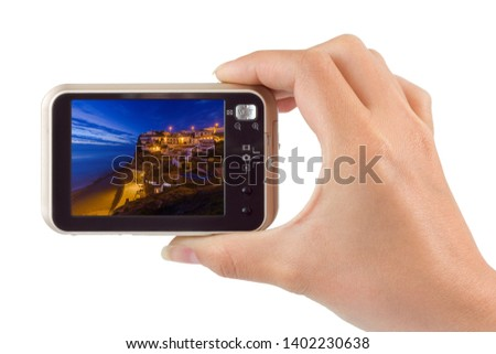 Hand with camera and Azenhas do Mar - Portugal (my photo) isolated on white background