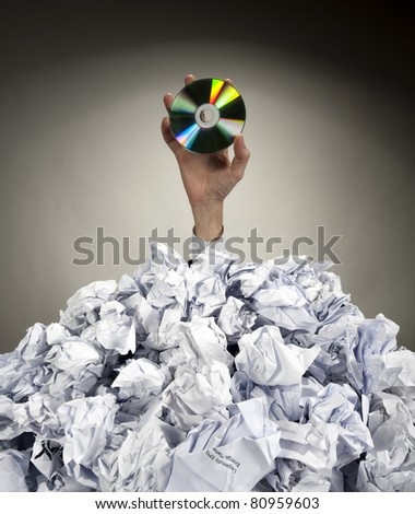 Hand with CD reaches out from big heap of crumpled papers