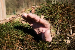 Hand with cigarette stub sticks out of grave covered with moss and dirt