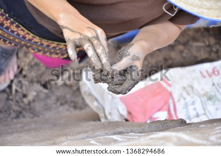 hand​ with​ clay.​  pattering the​ wall​ with​ clay.​ adobe​ house.​ clay​ house. dirty hand while building mud house.