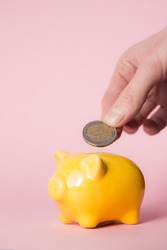Hand with coin and yellow piggybank with pink background