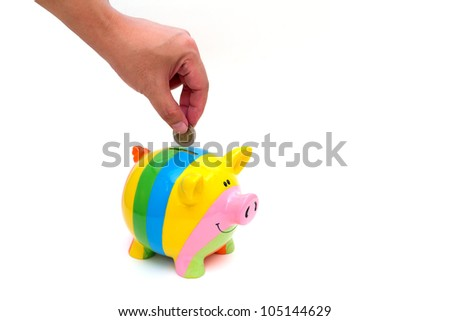 Hand with coin over a piggy bank on white background with reflection