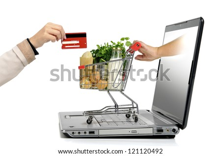 Hand with credit card and a small shopping cart coming from  laptop screen isolated in white - stock photo