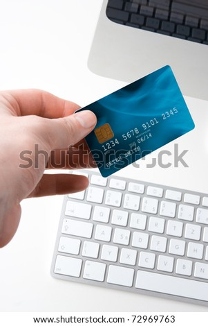Hand with credit card and computer - electronic payment concept. Focused on credit card. I am author of image used on credit card and used data are fictitious.