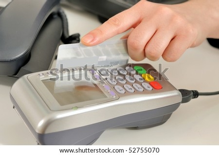 Hand with credit card swipe through terminal for sale.