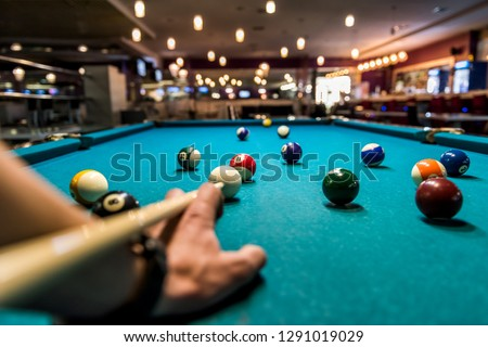 Hand with cue aiming on billiard ball at table