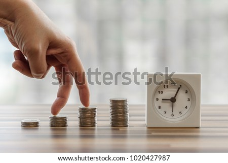 Hand with fingers business man putting on coin and looking for saving money, collect money with earning bank deposit interest and take time. Business ideas concept with blurred background