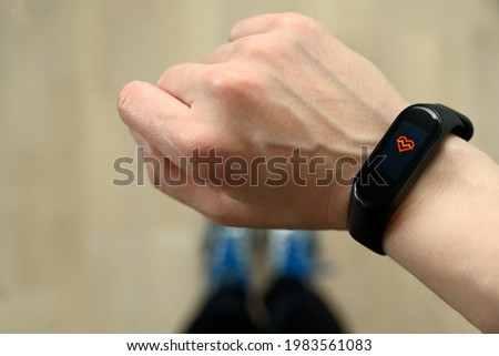 Hand with fitness tracker and sport shoes on background. Pulse mode, heart rate Foto stock ©