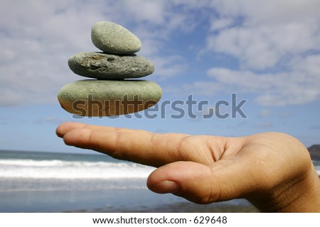 Hand with floating pebble stack; finding inner peace concept