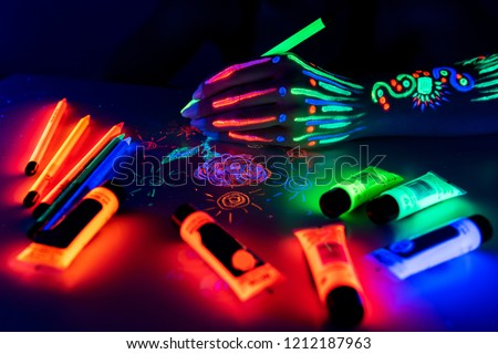 Hand with fluorescent ethnic pattern holding neon pencil. Fluorescent paint and pencil are on the table. Body Art concept