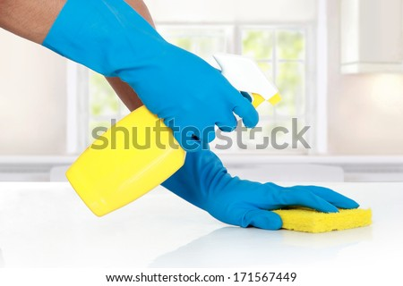 hand with glove using cleaning sponge to clean up the table