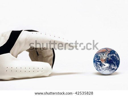 Hand with golf glove trying to capture the earth. Concept for world at my finger tips. Earth image from http://visibleearth.nasa.gov/