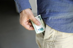 Hand with hundred euros and young men with money in the pocket