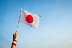 Hand with Japan red and white wristband holding a Japanese flag waving in soft blue sky