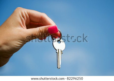 Hand with key against a blue sky