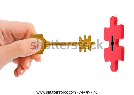 Hand with key and puzzle isolated on white background