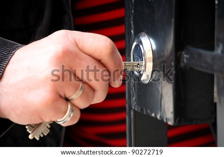 Hand with keys unlocking the front door, outdoor