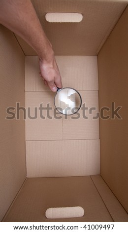 hand with loupe in cardboard box search something