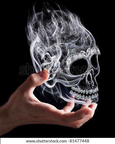 Hand with magical skull created by smoke as a symbol of black magic.